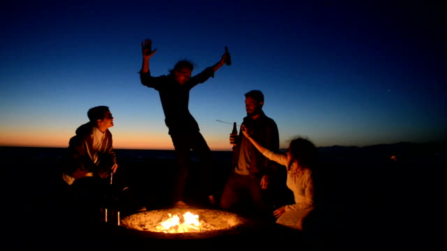 friends drinking beer at beach bonfire - cooler container stock videos and b-roll footage