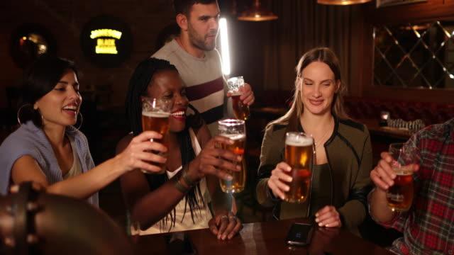 vidéos et rushes de amis buvant de la bière au bar dans le pub - bar