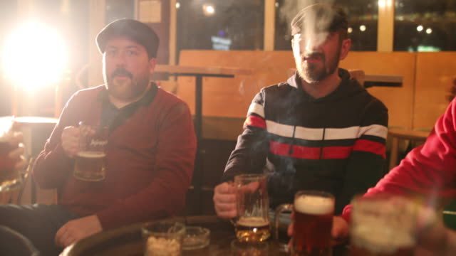 friends drinking beer at the pub - smoking issues stock videos & royalty-free footage