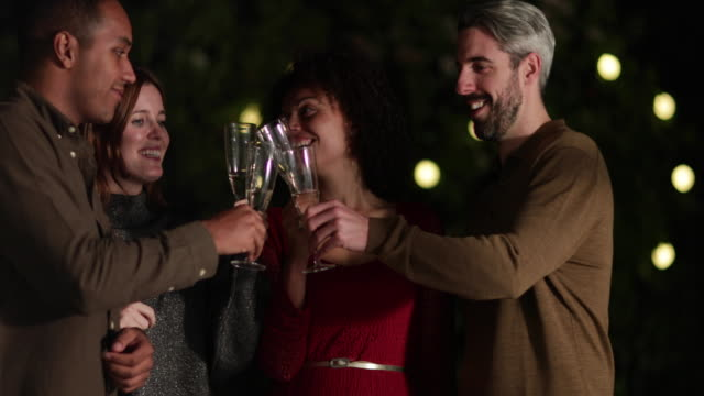 friends drinking champagne outdoors at night - vino video stock e b–roll