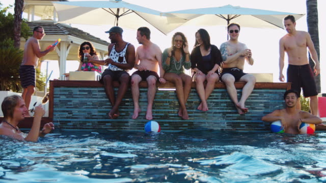 vídeos de stock e filmes b-roll de friends drinking on poolside and playing in water - ao lado da piscina
