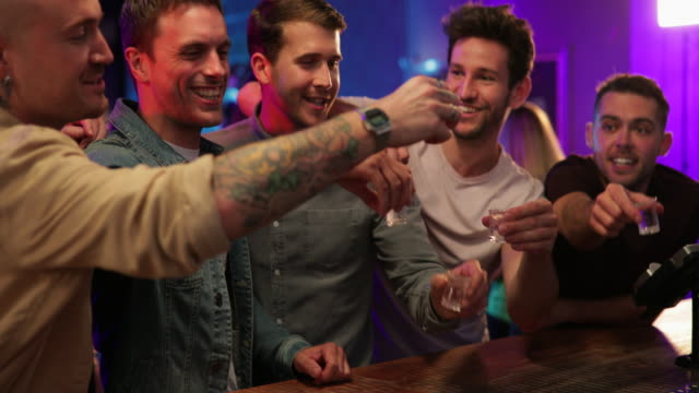 stockvideo's en b-roll-footage met vrienden drinken shots - bar tapkast