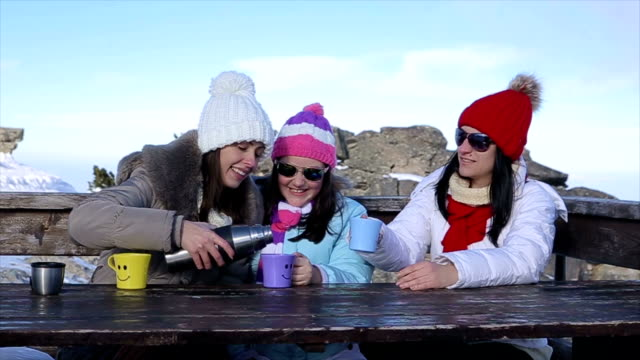 Friends drinking tea on the top of mountain at winter