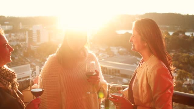freunde trinken wein auf dem balkon des gebäudes - gegenlicht stock-videos und b-roll-filmmaterial