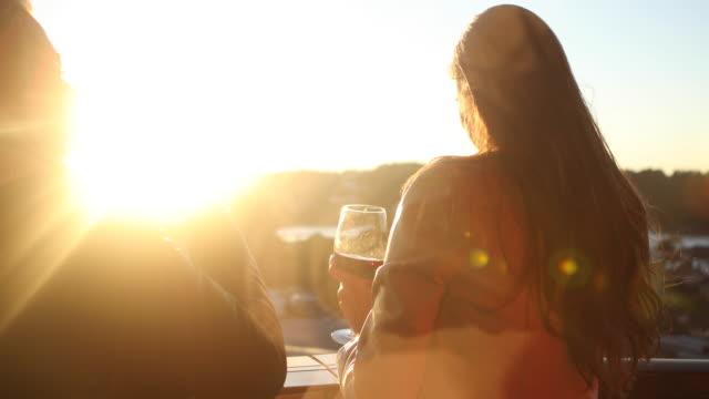 freunde trinken wein auf dem balkon des gebäudes - weinglas stock-videos und b-roll-filmmaterial
