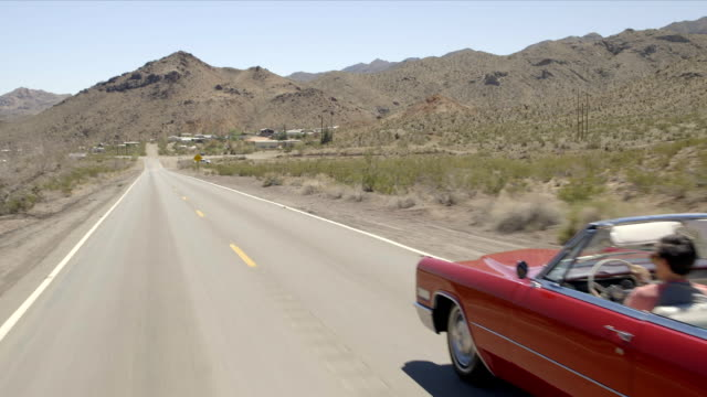friends drive through desert in red convertible - red convertible stock videos & royalty-free footage