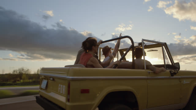 Friends driving classic Bronco throw hands in the air and cheer