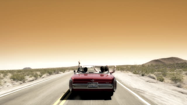vídeos de stock e filmes b-roll de friends driving through desert in classic convertible throw hands in the air - carro descapotável