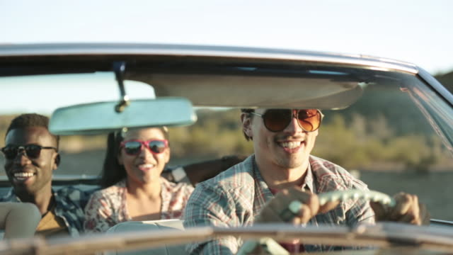 vidéos et rushes de friends driving through desert in red convertible throw arms in the air and cheer - véhicule terrestre
