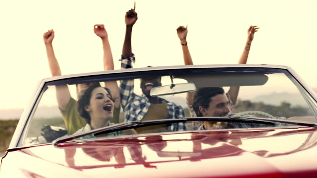 Friends driving through desert in red convertible throw hands in the air and cheer