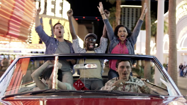 friends driving through downtown vegas in red convertible pump fists in the air and cheer - convertible stock videos & royalty-free footage