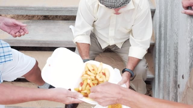 friends eat fish and chips on the beach - fish stock videos & royalty-free footage