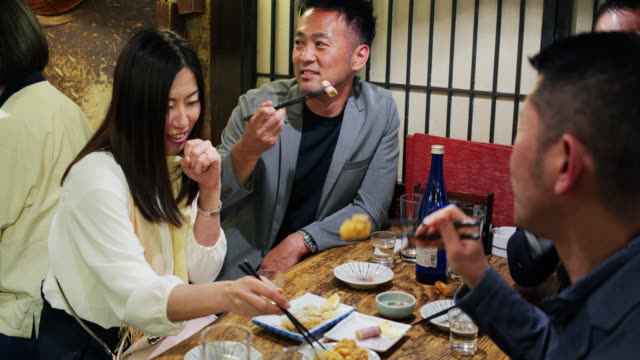 炉端レストランで食べる友達 - 居酒屋点の映像素材/bロール