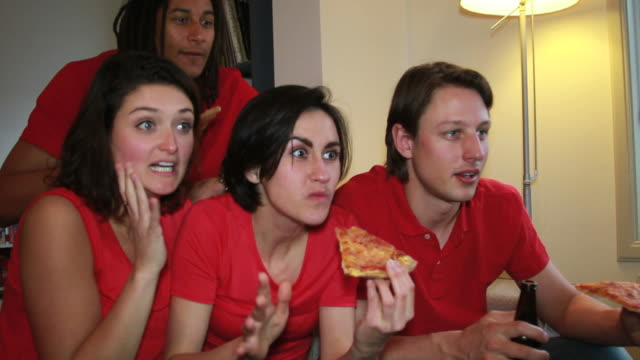 Friends eating pizza and watching television