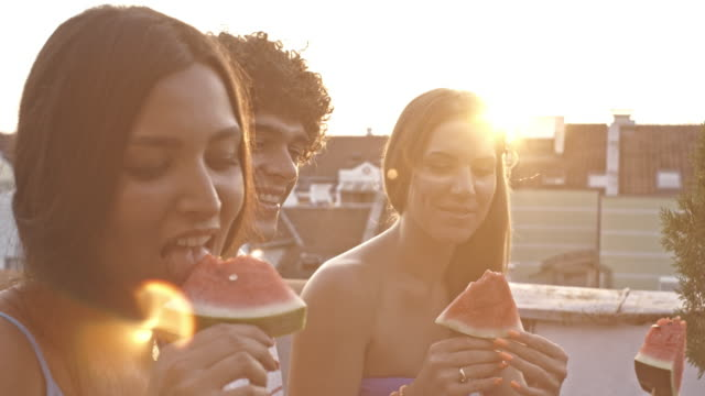 Friends eating watermelon on rooftop party
