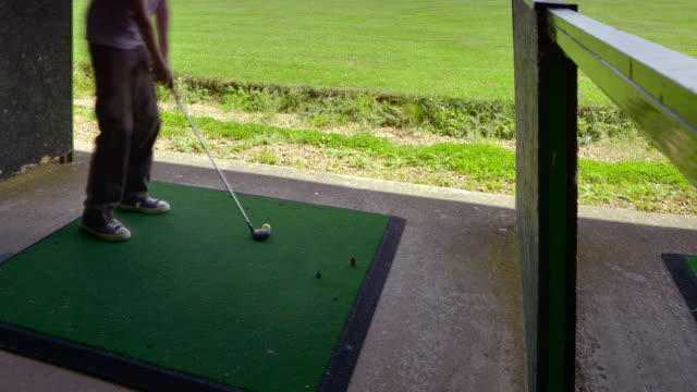 friends enjoy practising their golf swings at a golf driving range - driving range stock videos & royalty-free footage