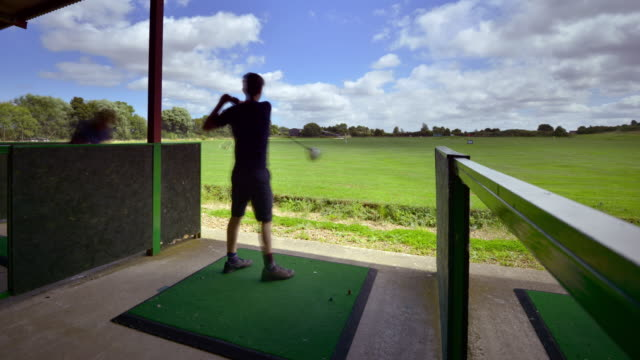 Friends enjoy practising their golf swings at a golf driving range