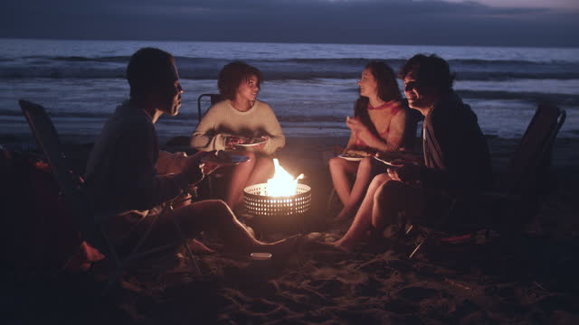 friends enjoying a campfire on the beach at night - social gathering stock videos & royalty-free footage