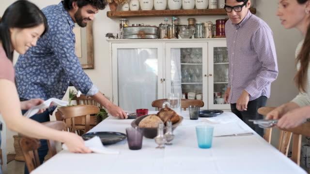 friends enjoying a vegan meal, friends setting the table before sharing a meal. - setting the table stock videos & royalty-free footage