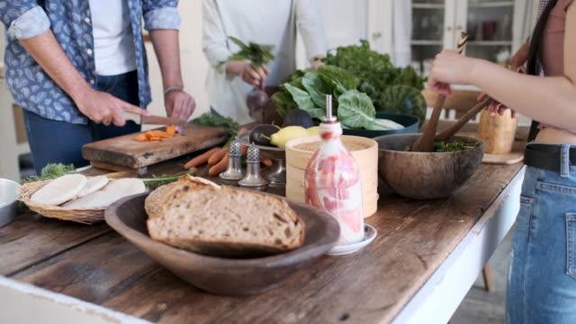 freunde genießen eine vegane mahlzeit - essen zubereiten stock-videos und b-roll-filmmaterial