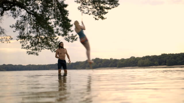 Friends enjoying and playing on rope swing over lake.