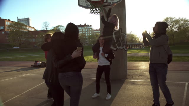 stockvideo's en b-roll-footage met friends enjoying at basketball court during sunny day - shirt met capuchon