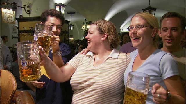 ms friends enjoying beer in hofbrauhaus, munich, bavaria, germany - 男性と複数の女性点の映像素材/bロール