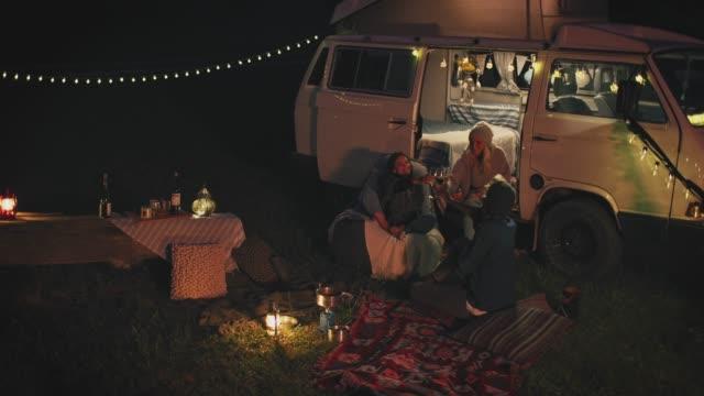 amici che si godono un drink mentre si rilassano di notte - furgone video stock e b–roll