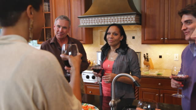 ms pan friends enjoying in kitchen before dinner party / albany, new york, united states  - dinnerparty stock-videos und b-roll-filmmaterial