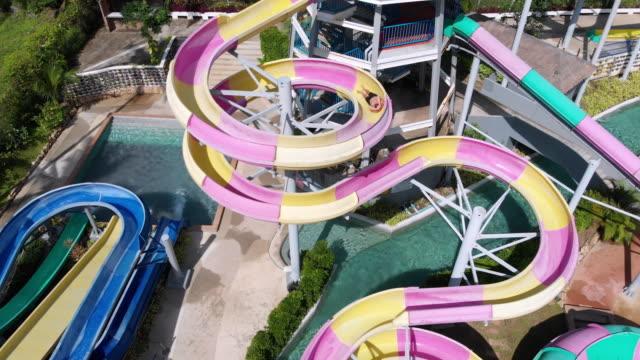 vídeos de stock, filmes e b-roll de amigos, desfrutando em slides no parque aquático - tobogã d'água
