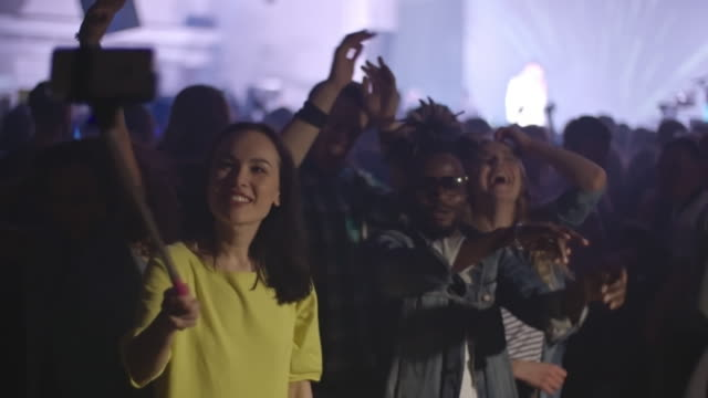 Friends filming themselves at pop concert