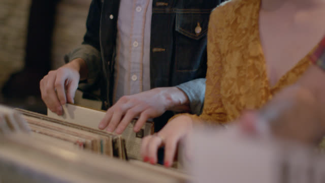 friends flip through stacks of vintage vinyl in crowded record store - pawnbroker stock videos & royalty-free footage