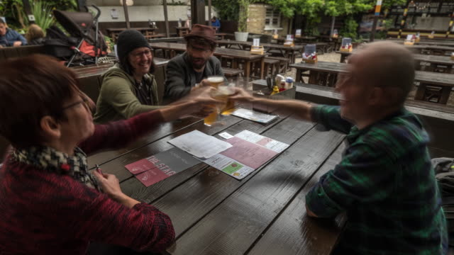 friends gather and enjoy a drink and traditional sunday roast in their local pub garden - roast dinner stock videos & royalty-free footage