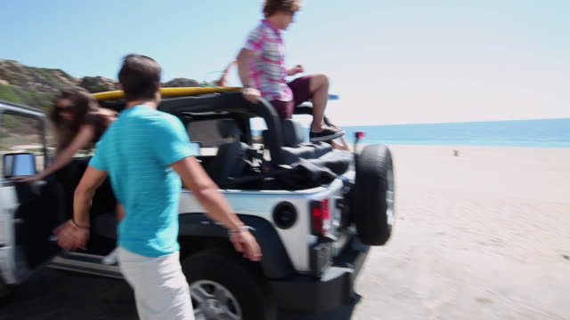 friends getting out of vehicle at the beach - fyrhjulsdrivet fordon bildbanksvideor och videomaterial från bakom kulisserna