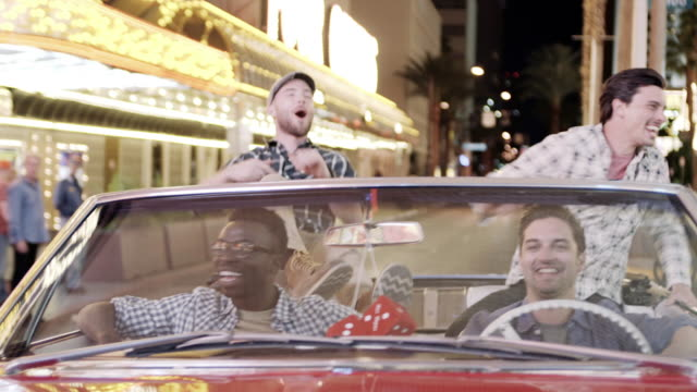 friends go wild cruising through downtown las vegas in classic convertible - 独身男性点の映像素材/bロール
