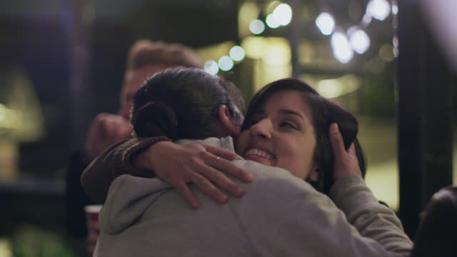 MS SLO MO. Friends greet man with handshakes and hugs at rooftop party.