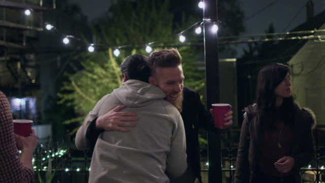 MS. Friends greet man with hugs at house party on Chicago rooftop.