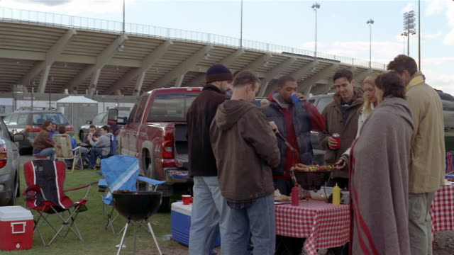 friends grilling hot dogs and shish kebabs and drinking beers at tailgate party on chilly day - checked pattern stock videos & royalty-free footage