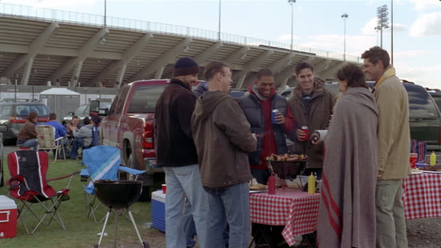 vídeos y material grabado en eventos de stock de friends grilling hot dogs and shish kebabs and drinking beers at tailgate party on chilly day - a cuadros