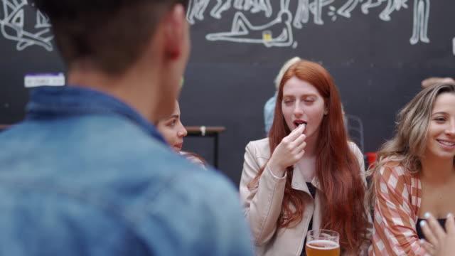 パブで仕事の後にぶらぶらしている友人 - 食品 ピーナッツ点の映像素材/bロール