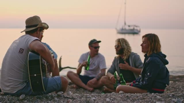 freunden rumhängen, zeitlupe trinken bier und gitarre am sunset beach, - in den dreißigern stock-videos und b-roll-filmmaterial