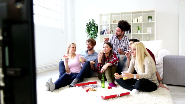 vídeos de stock e filmes b-roll de amigos, divertir-se comer pizza deliciosa e beber - sala de casa