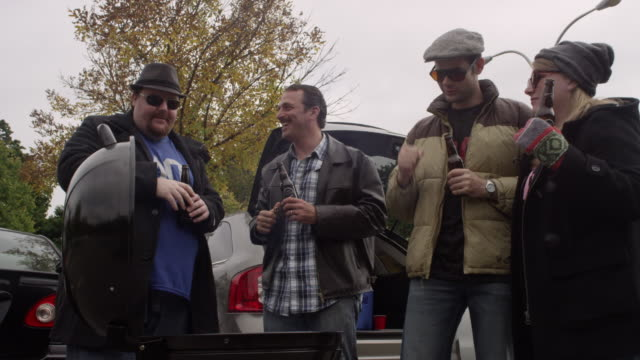 friends having a good time at a tailgating party - beer cap stock videos & royalty-free footage
