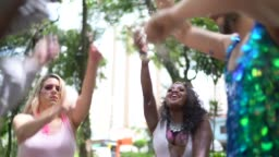 Friends having fun and dancing with confetti a carnival party in Brazil