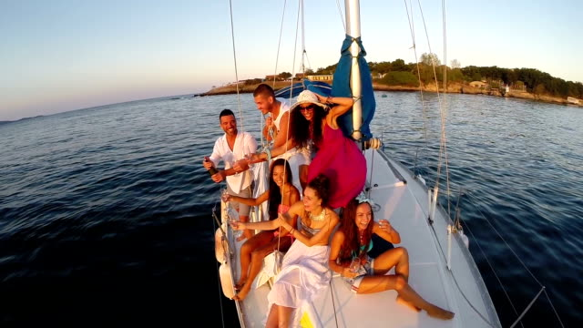 Friends having fun and drinking on yacht