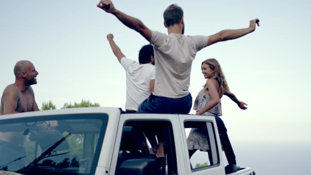 Friends having fun in a SUV with sun roof. Viewpoint