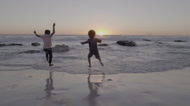 friends having fun in sea waves at beach - twilight stock videos & royalty-free footage
