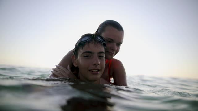 vidéos et rushes de amis ayant l'amusement dans la mer peu profonde sur des vacances d'été - jeunes garçons