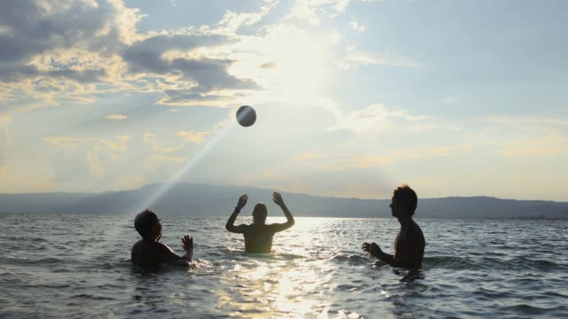 friends having fun in the sea with ball. playing volleyball until sunset at summer vacation - lighting technique stock videos & royalty-free footage
