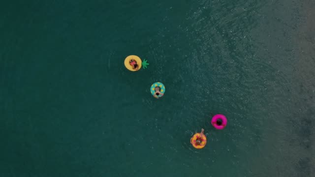 friends having fun on floaties in water - inflatable stock videos & royalty-free footage